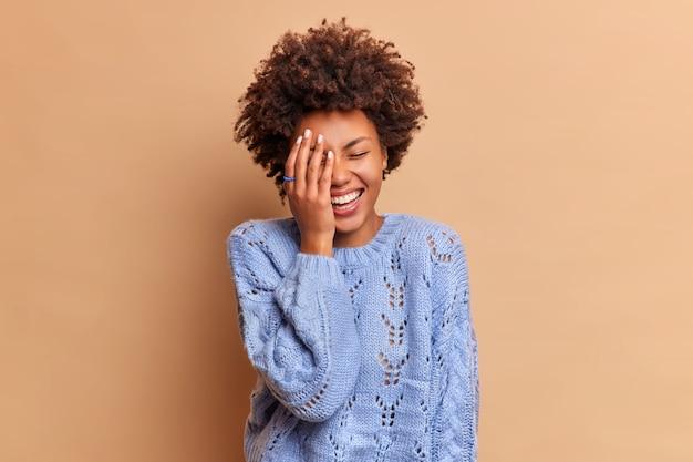 巻き毛の幸せなのんきな女性が面白い冗談から大声で笑う顔の手のひらがベージュの壁に隔離されたカジュアルなジャンパーを着て陽気な何かを見る