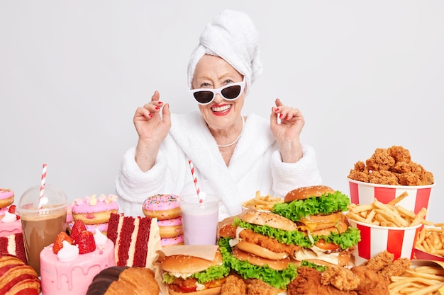 Happy carefree wrinkled lady smiles gladfully with sunglasses enjoys cheat meal day surrounded by junk food