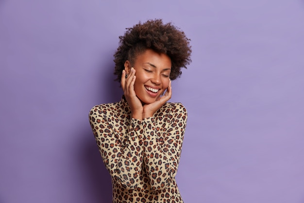 Happy carefree young afro american woman with natural beauty, curly hair, pleasant broad smile, touches face, enjoys soft skin, closes eyes in satisfaction