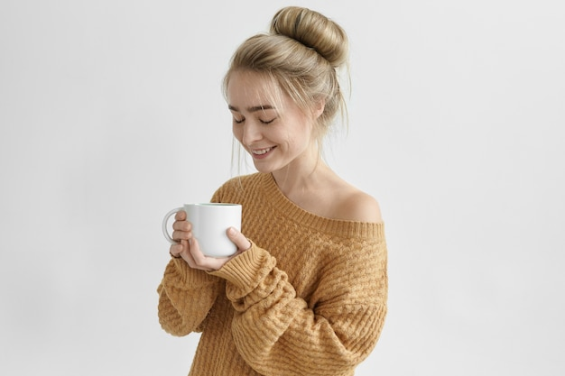 Happy carefree young woman with hair bun relaxing at home after work smiling broadly, enjoying good coffee from large mug. attractive female dressed in cozy warm sweater drinking herbal tea