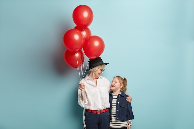Happy caring grandmother holds bunch of red air balloons, congratulates granddaughter with birthday