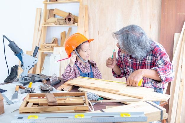幸せな大工の家族。木工店で木工をしながら手を挙げている少女とおじいさん。
