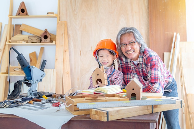 幸せな大工の家族。小さな女の子と祖父は、木造の店で木工をしている間、幸せそうに笑いました。