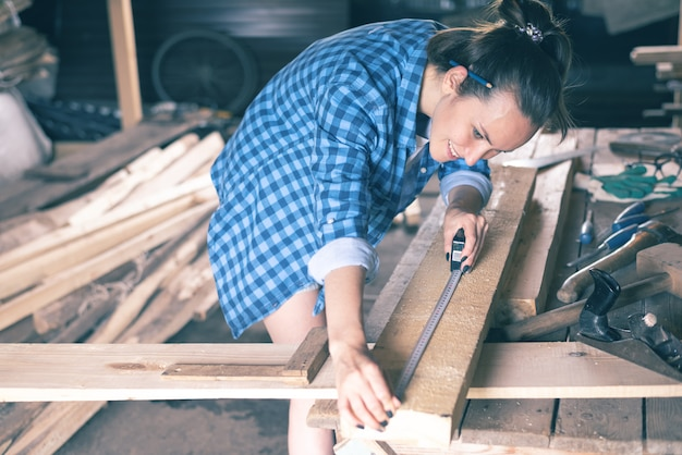 Happy carpenter woman measures a wooden board measuring tape in the home workshop
