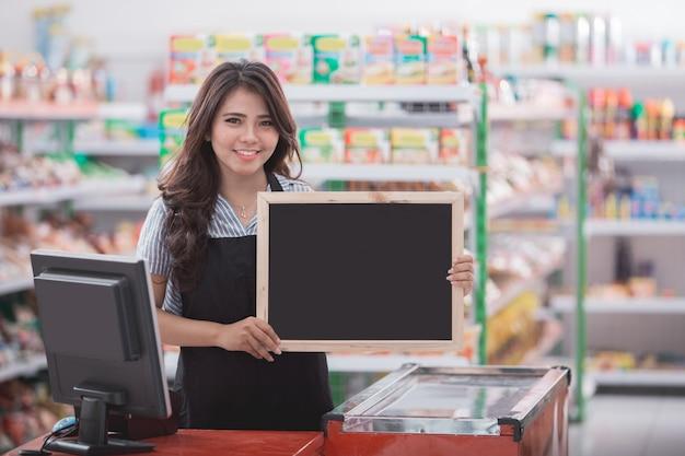 Happy cashier with blank blackboard