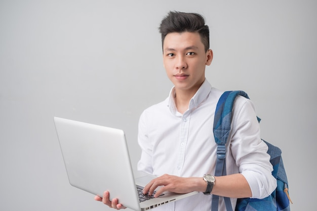 회색 배경에 격리된 노트북을 사용하는 행복한 캐주얼 아시아 남학생