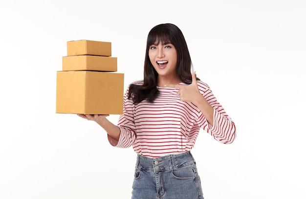 Счастливая случайная азиатская женщина, несущая коробку для доставки, которая была упакована для доставки, изолирована на белом фоне.