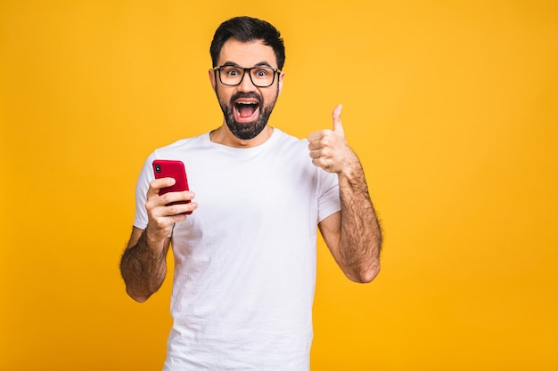 Happy casual bearded man with smartphone and thumb up isolated over yellow background.
