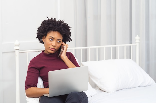 Happy casual beautiful american african woman working on laptop computer while setting  on the bed in the house.