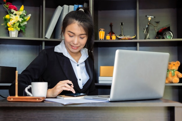 Happy casual beautiful asian business woman holding smartphone working on a laptop at office.