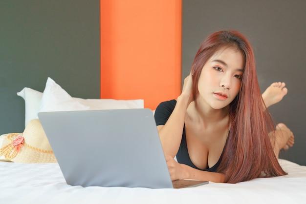 ベッドの上のラップトップに取り組んでいる幸せなカジュアルな美しい女性アジア人