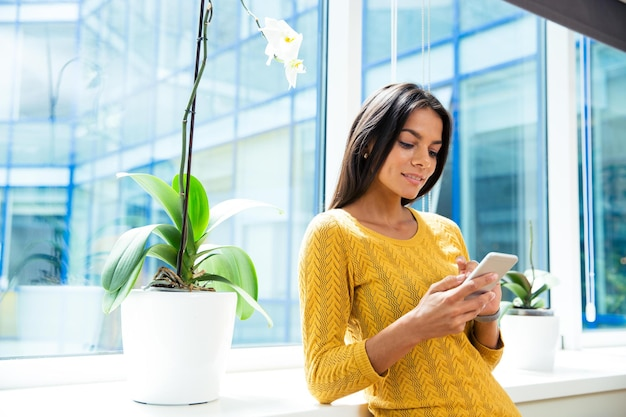 Счастливый случайный бизнесвумен с помощью смартфона в офисе возле окна