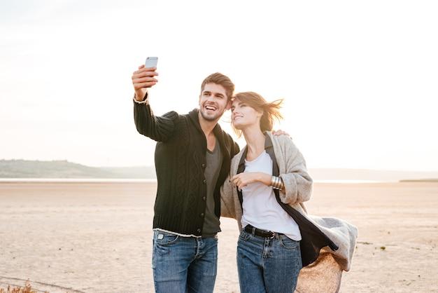 햇빛 아래 해변에 함께 서서 셀카 사진을 찍는 행복한 캐주얼 커플