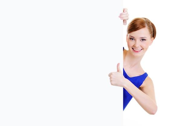 親指を立てて示す空白のバナーと幸せなカジュアルな女の子