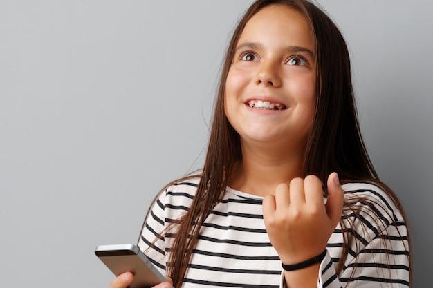 Счастливая вскользь маленькая девочка смотря ее телефон