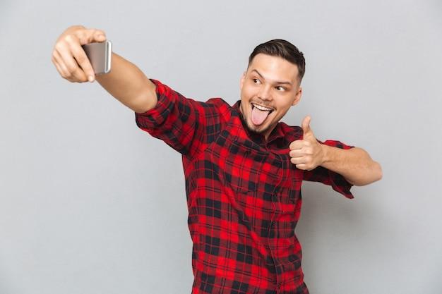 Selfieを作る格子縞のシャツで幸せなカジュアルな男