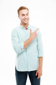 Счастливый случайный человек указывая пальцем в сторону copyspace, изолированного на белой стене