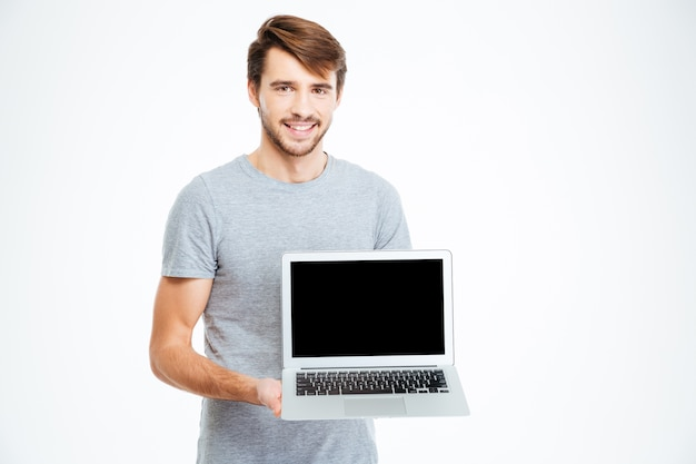 Happy casual man showing blank laptop computer screen isolated on a white background
