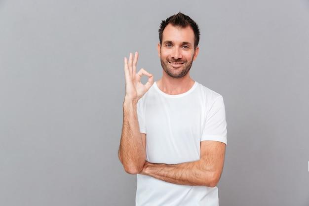 灰色の背景に分離された指でokサインを示す幸せなカジュアルな男