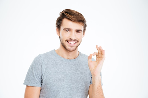 Happy casual man showing ok sign with fingers isolated on a white background