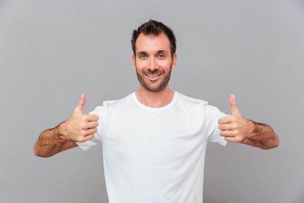 Счастливый случайный человек показывает палец вверх на сером фоне