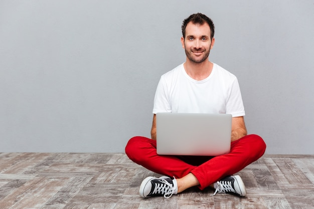 Счастливый случайный человек, сидящий на полу с ноутбуком на сером фоне