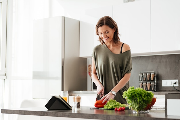 Happy casual woman cutting vegetables