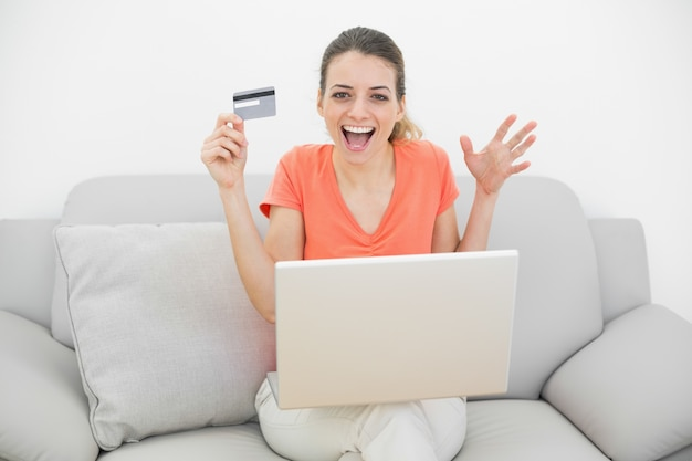 Happy casual woman showing her credit card using her notebook