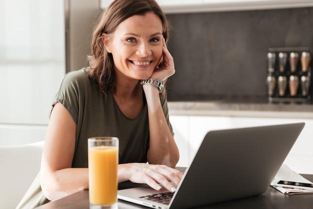 キッチンのジュースやタブレットコンピューターとテーブルのそばに座って幸せなカジュアルな女