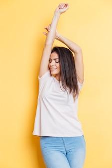 黄色の壁に立っている幸せなカジュアルな女性