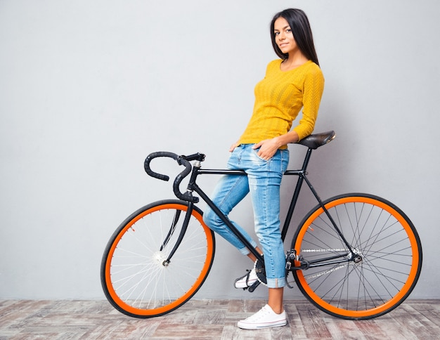 Happy casual woman standing with bicycle