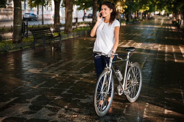 Happy casual woman talking on the phone and walking with bicycle at the city park
