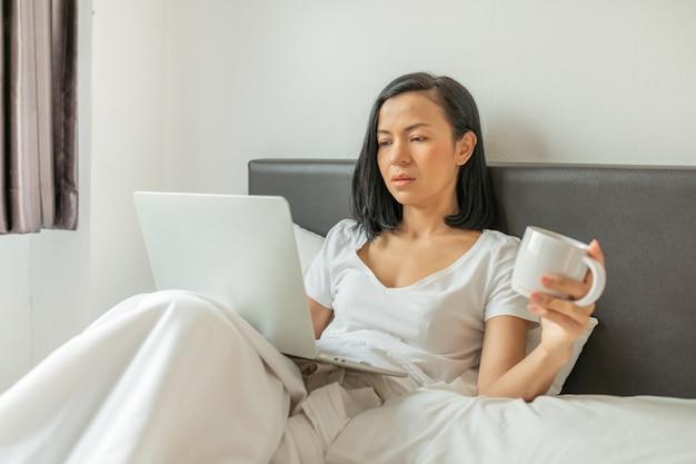 집에서 침대에 앉아 노트북에서 작업하는 행복 한 캐주얼 여자.