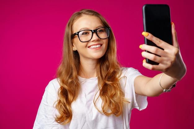 Счастливая случайная молодая женщина улыбается и имеет видеозвонок