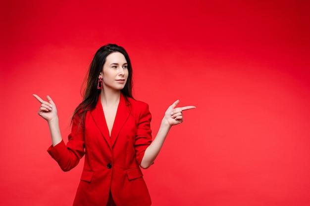 赤いオフィススーツで長く暗いストレートの髪を持つ幸せな白人女性が喜ぶ