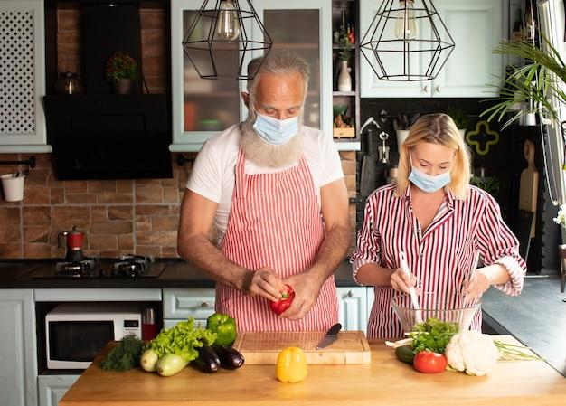 Счастливая пара кавказских в возрасте, готовящая дома в маске. делаем салат дома. домашняя еда. социальная дистанция. готовим во время covid 19.