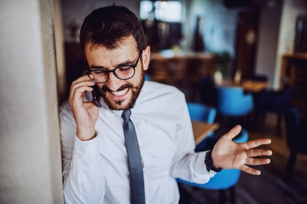 Happy caucasian bearded handsome businessman in shirt and tie and with eyeglasses calling his mistress while leaning on wall in cafe.