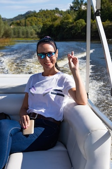Happy caucasian beautiful woman on the pine forest of a luxury yacht