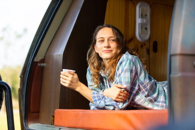 幸せな白人の美しい女性旅行者の人々は、キャンピングカーでコーヒーの朝の自然休暇を楽しんでいます