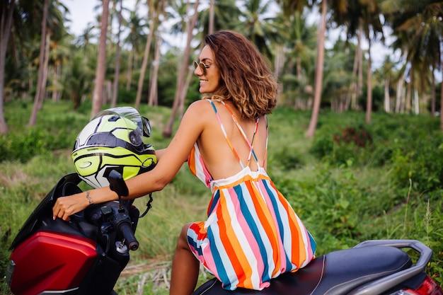 Felice motociclista caucasico donna in abito estivo colorato in vacanza con casco da motociclista