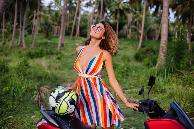 오토바이 헬멧 휴가에 화려한 여름 드레스에 행복 백인 자전거 타는 여자