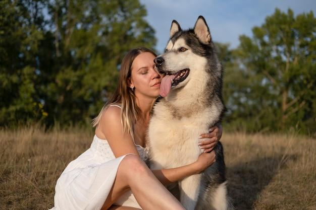 Счастливая кавказская белокурая женщина в белом платье обнимает собаку аляскинского маламута в летнем поле. лицом к лицу. любовь и дружба между человеком и животным.