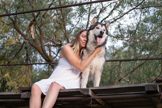 Счастливая кавказская белокурая женщина в белом платье обнимает собаку аляскинского маламута на подвесном мосту. лицом к лицу. крупным планом. любовь и дружба между человеком и животным.