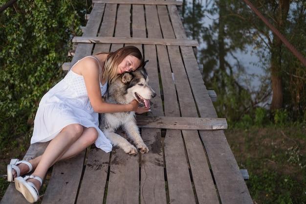 Счастливая кавказская белокурая женщина в белом платье обнимает собаку аляскинского маламута на подвесном мосту. лицом к лицу. вид сверху. любовь и дружба между человеком и животным.