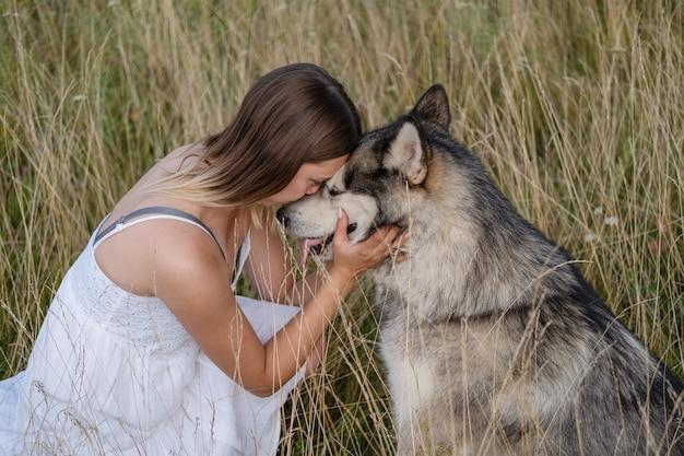 Счастливая кавказская белокурая женщина в белом платье обнимает и целует собаку аляскинского маламута в летнем поле. лицом к лицу. любовь и дружба между человеком и животным.