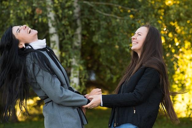 日当たりの良い秋の公園で笑っている幸せな白人ブルネットの女の子の友達。