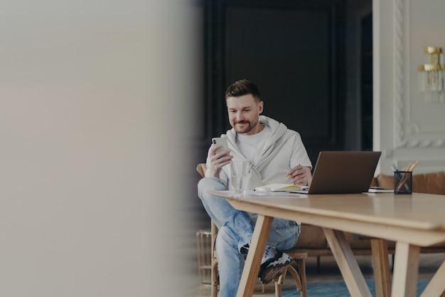 ノートパソコン、本、鉛筆をガラスに入れたテーブルで働きながら、携帯電話を使って足を組んで楽しい気分の幸せな白人のビジネスマン。自宅からリモートで働く男性フリーランサー
