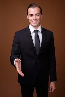 Счастливый кавказский бизнесмен улыбается и дает рукопожатие