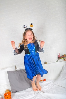Happy caucasian child girl in a dress and a witch hat, with buckets of sweets at home copy space