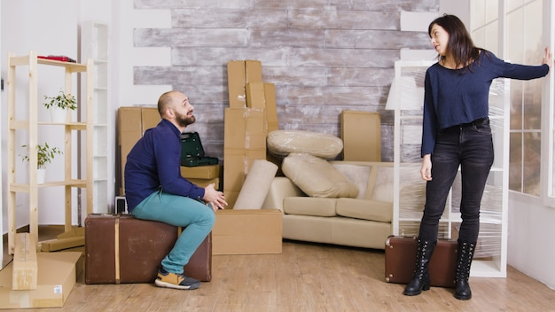彼らの新しいアパートでスーツケースを運ぶ幸せな白人カップル。バックグラウンドで段ボール箱。